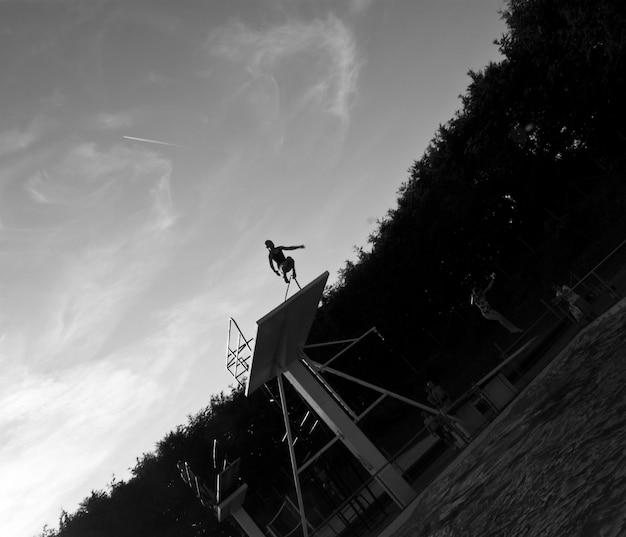 Ujęcie w skali szarości przedstawiające osobę skaczącą z deski do basenu