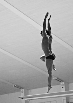 Ujęcie w skali szarości przedstawiające osobę skaczącą z deski do wody