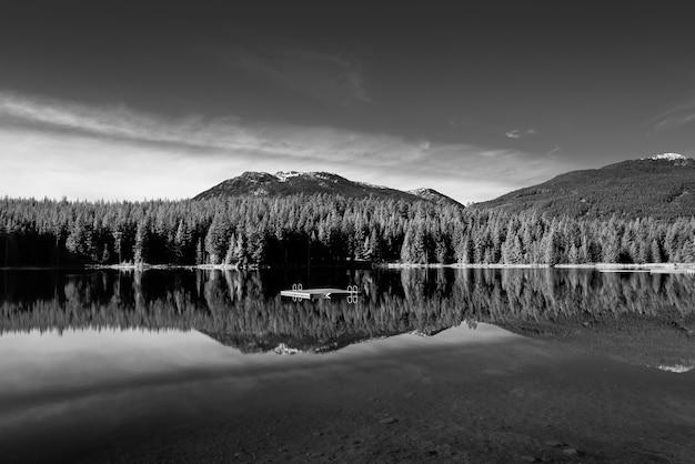 Ujęcie w skali szarości przedstawiające piękną scenerię odbijającą się w lost lake, whistler, bc kanada