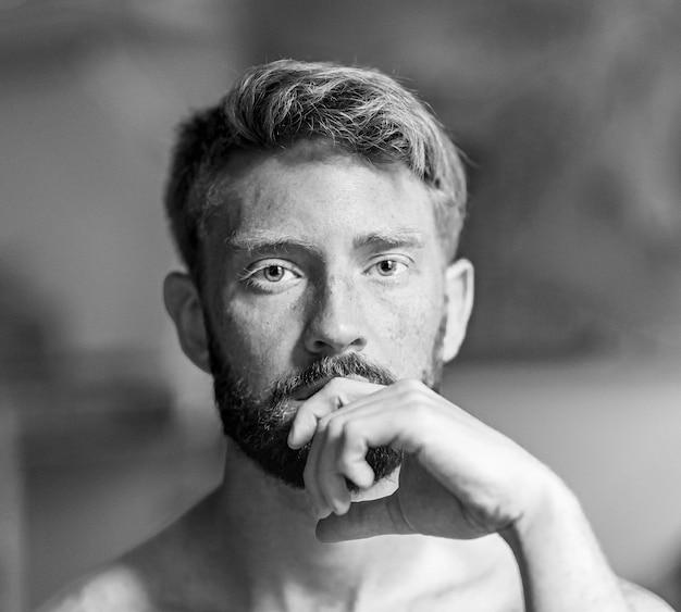 Ujęcie w skali szarości przedstawiające przystojnego mężczyznę rasy kaukaskiej z ręką na brodzie