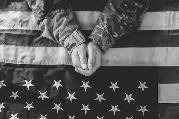 Ujęcie w skali szarości przedstawiające żałobnego i modlącego się amerykańskiego żołnierza z amerykańską flagą przed sobą