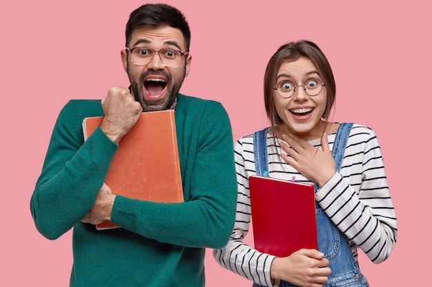 Ujęcie w studio przedstawiające uszczęśliwioną kobietę i mężczyznę zaciskających ze szczęścia pięści, czujących się zadowolonych z ukończenia uniwersytetu, trzymających podręczniki, wpatrujących się
