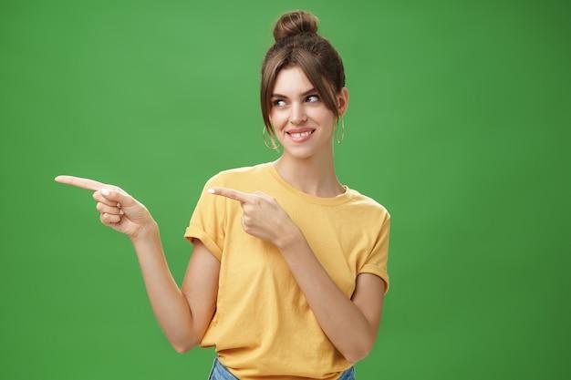 Ujęcie w talii charyzmatycznej, szczęśliwej i beztroskiej uroczej kobiety w żółtej koszulce, wskazującej i patrzącej ...