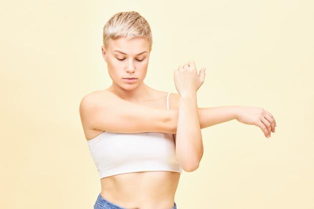 Ujęcie w talii pięknej modnej młodej kobiety z chłopięcą fryzurą, skoncentrowanej na swoich uczuciach podczas rozciągania mięśni ramion, przyciskania ramienia i łokcia do klatki piersiowej