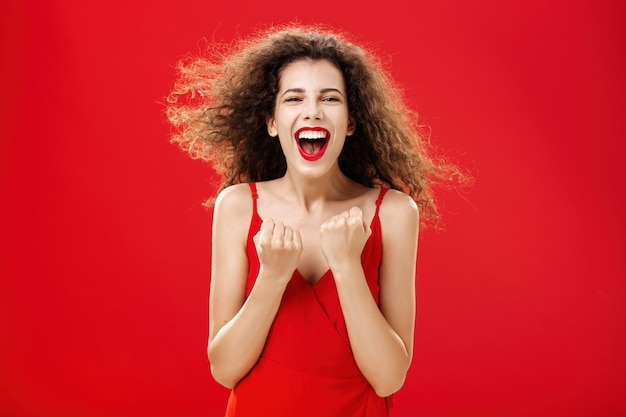 Ujęcie w talii udanej, zadowolonej i zachwyconej, szczęśliwej kobiety z kręconymi włosami w stylowej sukience zaciśniętej...