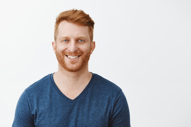 Ujęcie w talii uroczego rudowłosego dojrzałego europejczyka z włosiem i pięknymi, naturalnymi niebieskimi oczami stojącego nad szarą ścianą w niebieskiej koszulce, uśmiechającego się