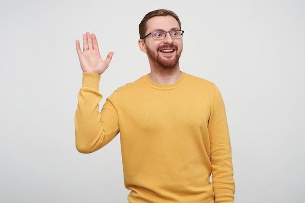 Ujęcie wesołego, młodego, przystojnego brązowowłosego brodatego faceta w okularach, podnoszącego dłoń w geście powitania, patrząc pozytywnie na bok ze szczerym uśmiechem, pozującego w musztardowym swetrze