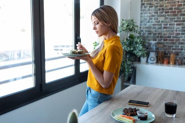 Ujęcie wesołej pięknej kobiety jedzącej sałatkę przed oknem w kuchni