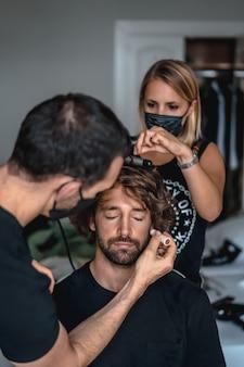Ujęcie wizażysty, fryzjera w maskach medycznych, wykonującego swoją pracę