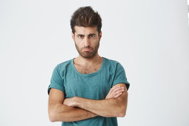 Ujęcie wściekłego, zrzędliwego młodego mężczyzny ubranego od niechcenia z założonymi rękami, patrzącego z surowym i sceptycznym wyrazem, nie wierzy w wymówki swojej niewiernej dziewczyny
