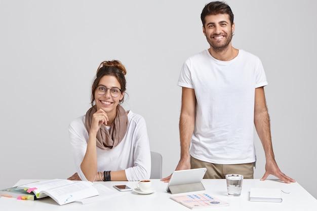 Ujęcie współpracowników kobiety i mężczyzny w białych ubraniach, patrzenie z radosnymi minami, wspólna praca nad wspólnym zadaniem, pozowanie w pobliżu miejsca pracy, na białym tle