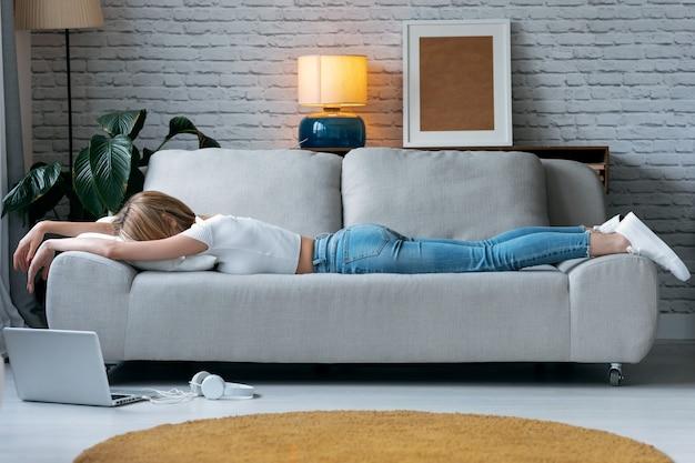 Ujęcie wyczerpanej młodej kobiety leżącej na kanapie w domu.