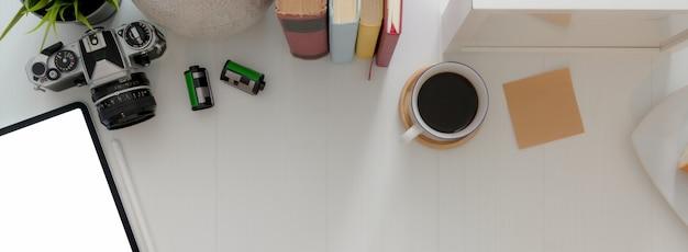 Ujęcie z biurka domowego biura z miejsca kopiowania, książek, aparatu, filiżanki kawy i dekoracji