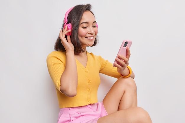 Ujęcie z boku dobrze wyglądającej kobiety o ciemnych włosach o wschodnim wyglądzie słucha muzyki przez słuchawki, pobiera piosenkę na playlistę, ma na sobie żółty podkoszulek i spódnicę na białym tle na białej ścianie