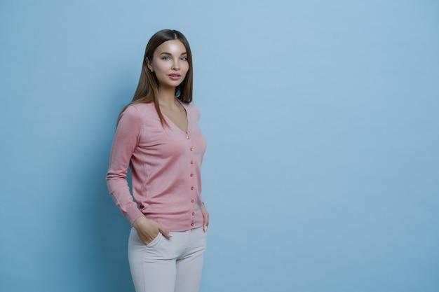 Ujęcie z boku pięknej ciemnowłosej młodej kobiety europejskiej nosi stylowy sweter, trzyma ręce w kieszeni białych spodni