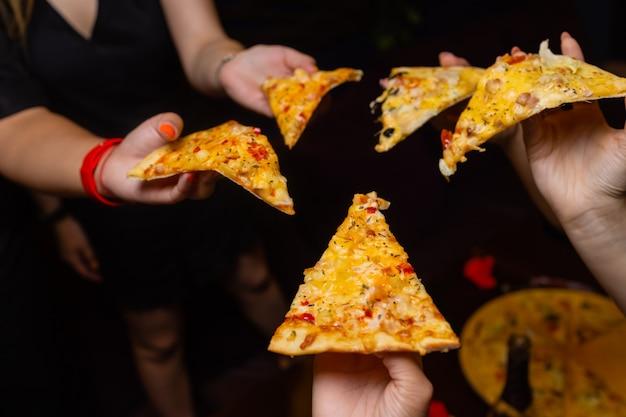 Ujęcie z dużego kąta ujęcia dłoni nierozpoznawalnych osób, które chwytają kawałek pizzy.