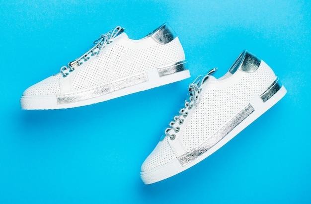 Ujęcie z góry butów do biegania. bliska, nowoczesne modne buty wykonane ze sznurowadeł. trampki na białym tle na niebieskim tle, moda. białe buty. para białych butów na niebieskim tle.