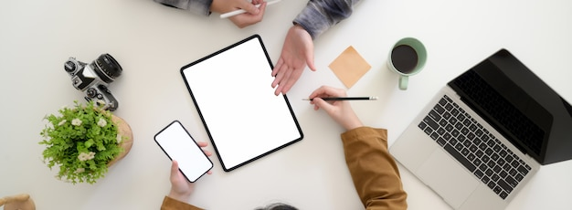 Ujęcie z góry dwóch kobiet-grafików omawiających swój projekt w nowoczesnym miejscu pracy