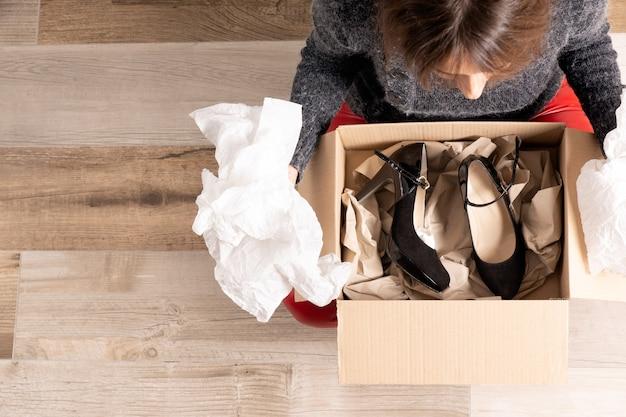 Ujęcie z góry młodej dziewczyny w czerwonych spodniach siedzącej na drewnianej podłodze, otwierającej paczkę, którą właśnie kupiła w internecie, zawierającą czarne buty na obcasie