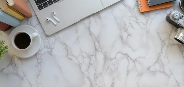 Ujęcie z góry nowoczesnego stanowiska fotografa z laptopem i akcesoriami biurowymi na marmurze
