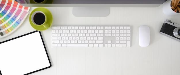 Ujęcie z góry obszaru roboczego projektanta z tabletem z pustym ekranem, urządzeniem komputerowym i materiałami projektowymi