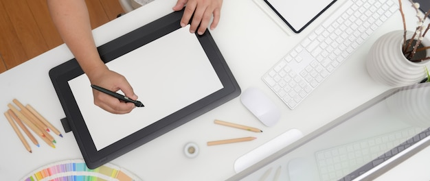 Ujęcie z góry projektanta pracującego na cyfrowym tablecie, urządzeniu komputerowym i projektantach