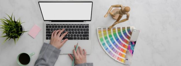 Ujęcie z góry projektanta pracującego na makietach laptopa i projektantów na marmurowym stole