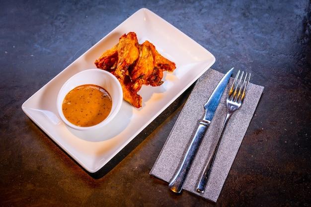 Ujęcie z góry skrzydełek z sosem barbecue na czarnym tle, na białym talerzu