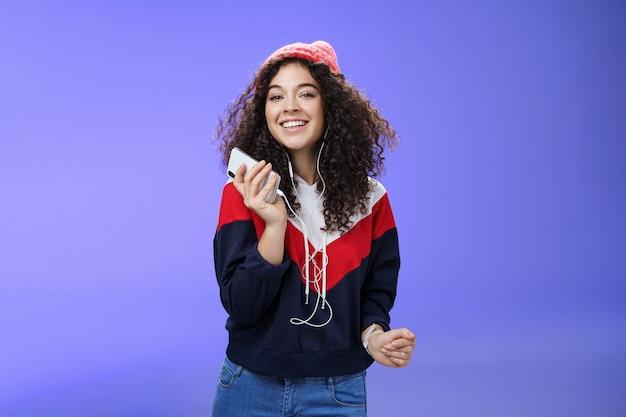 Ujęcie z góry urocza, szczęśliwa, delikatna, kręcona kobieta w czapce i bluzie słuchająca muzyki...