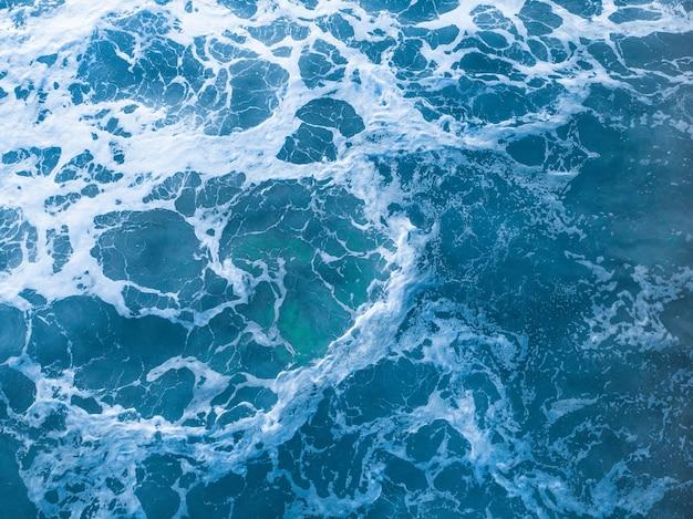 Ujęcie z lotu ptaka falującego błękitnego morza — idealne na urządzenia mobilne