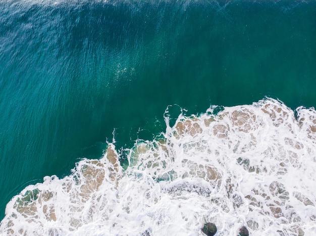 Ujęcie z lotu ptaka przedstawiające faliste, błękitne morze - idealne dla