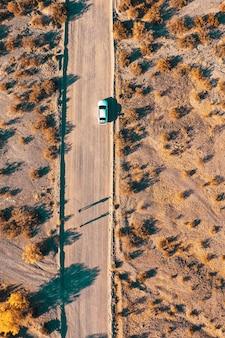 Ujęcie z lotu ptaka z drona w wąskiej pustynnej drodze z samochodem na poboczu drogi