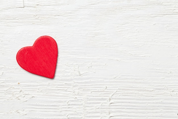 Ujęcie z małym czerwonym sercem na białym tle drewnianych - romantyczna koncepcja