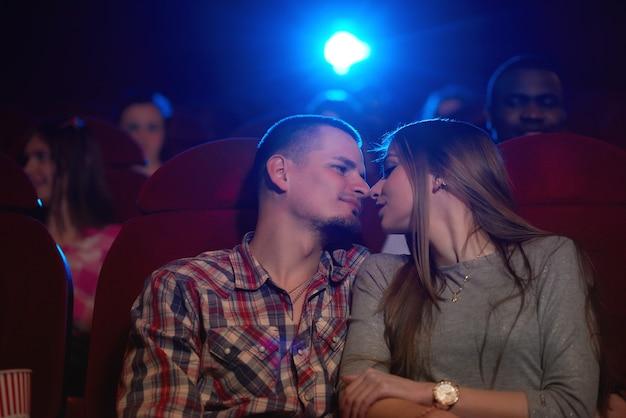Ujęcie z niskiego kąta młodej pary kochającej się, dzielącej romantyczne chwile na randce w kinie dotykając nosami miłość romans uczucia pary związki randki rozrywka rozrywka.
