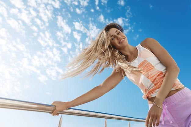 Ujęcie z niskiego kąta szczęśliwej, beztroskiej, aktywnej sportsmenki przeciw niebu w sportowej odzieży opartej na metalowym drążku