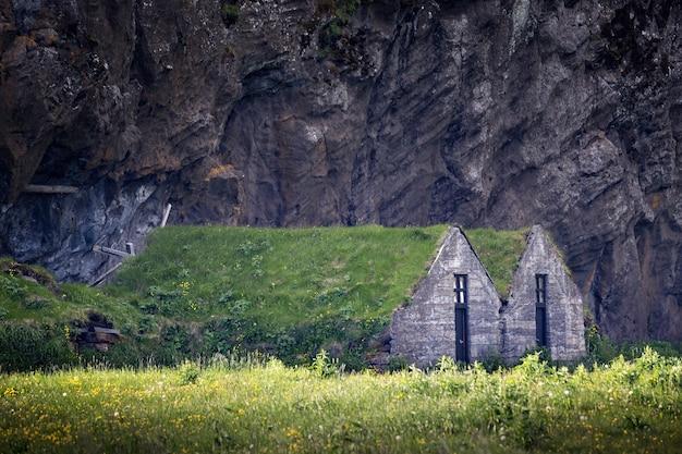 Ujęcie z poziomu oczu dwóch kamiennych domów z dachami z trawy na polu pod klifem w islandii