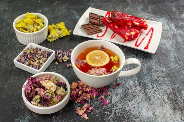 Ujęcie z przodu filiżanki herbaty ziołowej z miskami suchych kwiatów i tabliczką czekolady na szarym tle