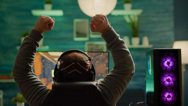 Ujęcie z tyłu szczęśliwego gracza wygrywającego strzelankę z perspektywy pierwszej osoby, grającej online na potężnym komputerze osobistym rgb, podnoszącym ręce. pro cyber występujący podczas wirtualnego turnieju za pomocą sieci technologicznej