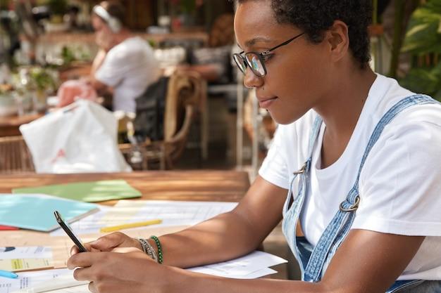 Ujęcie z ukosa afroamerykańskiego blogera rozmawiającego online, czyta wiadomości na stronie internetowej