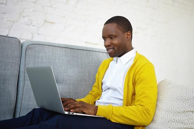 Ujęcie z ukosa atrakcyjnego, utalentowanego ciemnoskórego mężczyzny copywritera w stylowym stroju, siedzącego na kanapie w domu z przenośnym komputerem na kolanach, piszącego na klawiaturze nowy artykuł do internetowego magazynu internetowego