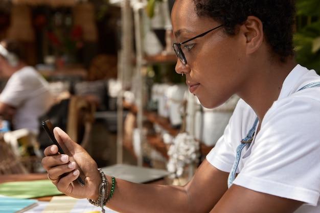 Ujęcie z ukosa czarnego nastolatka w przezroczystych okularach