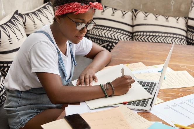 Ujęcie z ukosa czarnej, zajętej dziennikarki studiującej prace do napisania artykułu