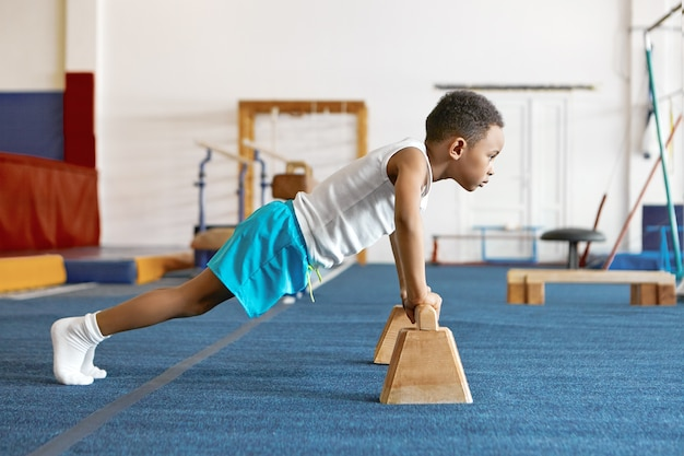 Ujęcie z ukosa skoncentrowanego, poważnego afroamerykańskiego dzieciaka w sportowym ubraniu, trzymającego stopy na podłodze