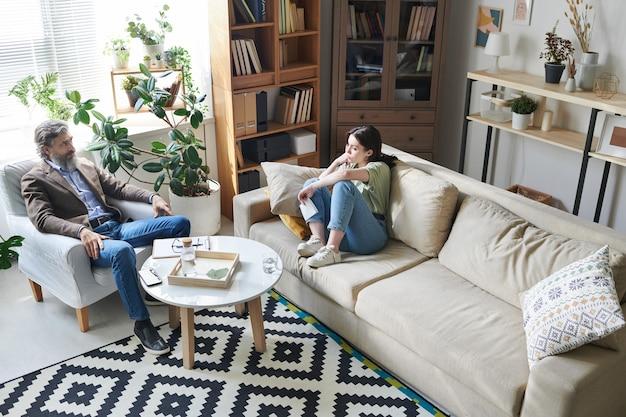 Ujęcie Z Wysokiego Kąta Profesjonalnego Psychologa Słuchającego Młodej Kobiety Z Depresją Podczas Sesji Terapeutycznej, Kopia Przestrzeń Premium Zdjęcia