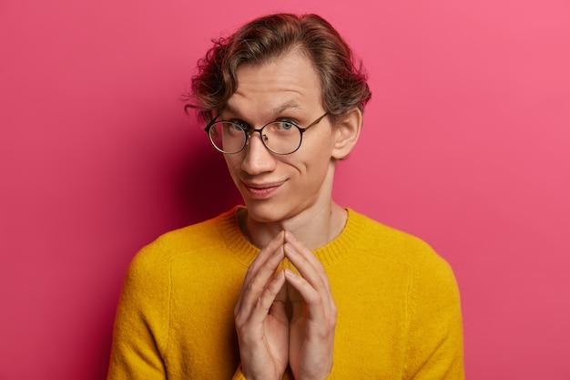 Ujęcie zaciekawionego młodego mężczyzny rasy kaukaskiej stukającego palcami, patrzy z zamiarem zrobienia czegoś, nosi okrągłe okulary i żółty sweter, ma w głowie jakieś plany, odizolowany na różowej ścianie