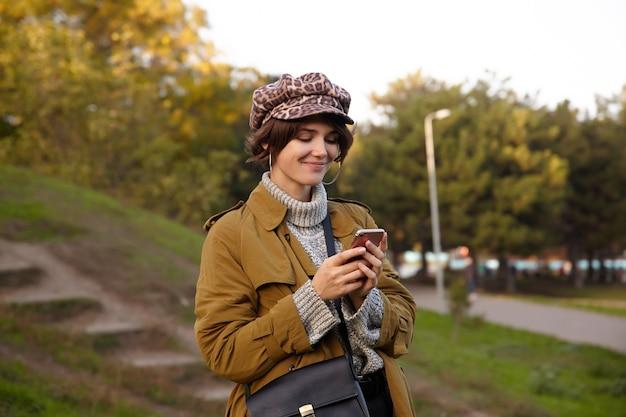 Ujęcie zadowolonej młodej uroczej brunetki z naturalnym makijażem w modnych ubraniach podczas spaceru po miejskim ogrodzie, uśmiechnięta wesoło podczas pisania wiadomości do swojej przyjaciółki