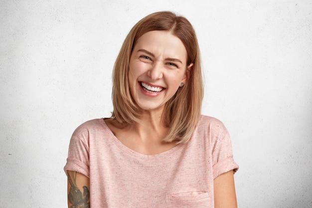 Ujęcie zadowolonej modelki marszczy brwi ze śmiechu, będąc w dobrym nastroju słysząc zabawną historię od koleżanki, ubrana niedbale, spędza wolny czas w domu.