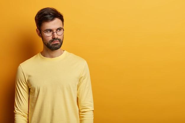 Ujęcie zamyślonego, brodatego europejczyka rozważającego decyzję, nosi okrągłe okulary i swobodny żółty sweter, kopiuje miejsce na treści reklamowe, zastanawia się nad pomysłem, ma spokojny wyraz twarzy.
