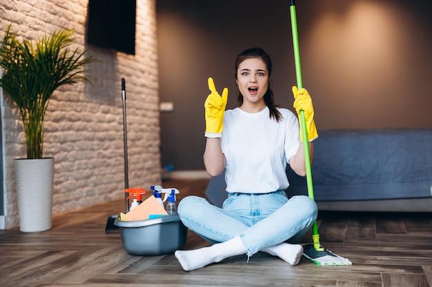 Ujęcie zdziwiona sprzątaczka w żółtej rękawicy trzyma mopa w salonie