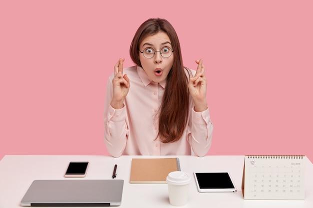 Ujęcie zdziwionej europejki ze zdumionym wyrazem twarzy, trzymającej ręce w geście modlitwy, ubranej w elegancką koszulę, będącej perfekcjonistką w biurze